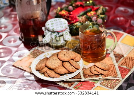 ginger biscuits with tea and jar of jam on a New Year's background