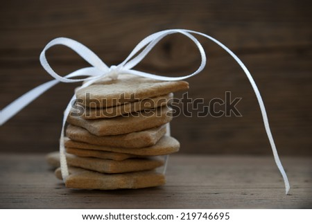 Ginger Bread Cookies with white Ribbon Bow on Wood, Food Background with Copy Space - stock photo