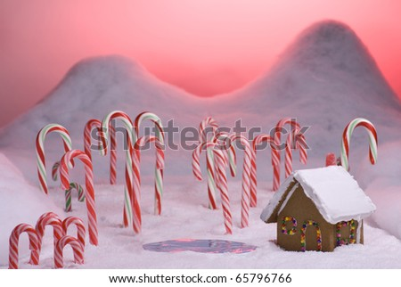 Ginger bread cottage next to a pond in candy cane forest with pink sunset - stock photo