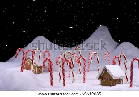 Ginger bread cottages in a snow covered candy cane forest and a star lit sky - stock photo