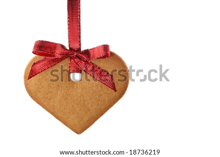 Ginger bread heart and red bow isolated on white background - stock photo