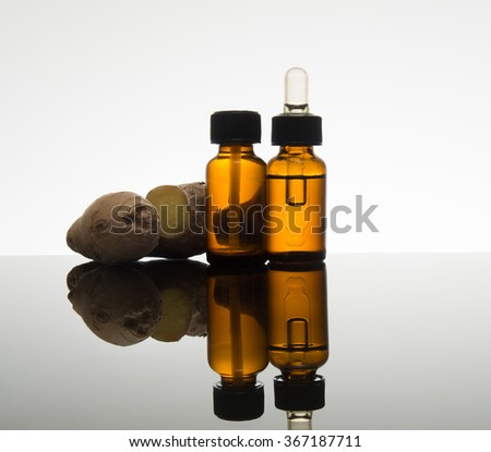Ginger essential oil in  amber bottle with fresh ginger root and dropper - stock photo