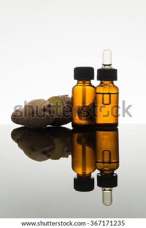 Ginger essential oil in amber glass bottle with ginger root and dropper