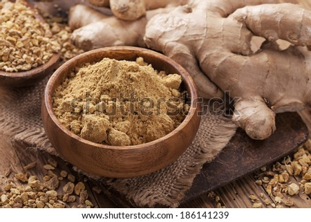 Ginger fresh root and ginger spice on a wooden table - stock photo