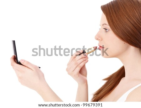 Ginger girl putting on lipstick, using mirror, side view. - stock photo