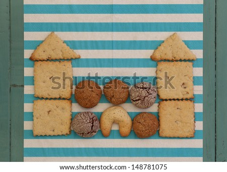 Ginger, Hazelnut and Chocolate Cookies Stacked as castle on blue striped napkin and turquoise wooden board, copy space - stock photo