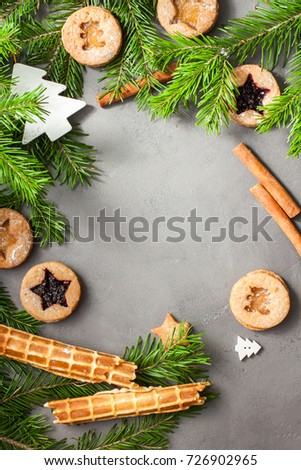 Ginger homemade cookies with strawberry jam on gray concrete background with Christmas tree.  View with copy space. Flat lay, top view. Christmas Border -banner.