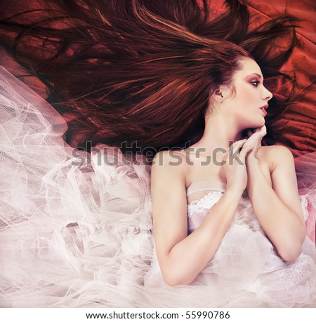 Ginger long haired young woman in sensual pose - stock photo