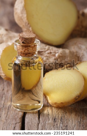 ginger oil in a glass bottle close-up, against the background of the root. Vertical - stock photo