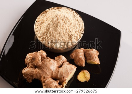 Ginger Powder with pieces of fresh ginger - stock photo
