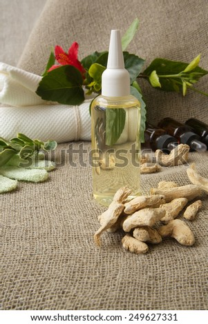 Ginger root hair oil. Ginger roots in the background - stock photo