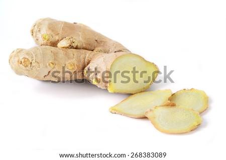 Ginger root sliced on white background. - stock photo