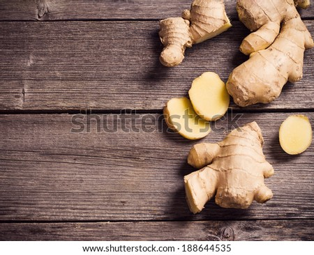 Ginger root sliced on wooden background - stock photo
