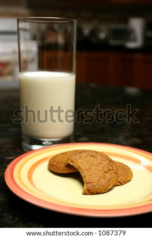 Ginger snaps over a plate in a black marble surface and glass of milk and one cookie bitten