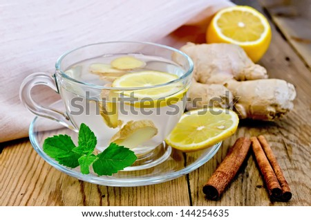 Ginger tea in a glass cup, lemon, cinnamon, ginger, mint, napkin against a wooden board - stock photo