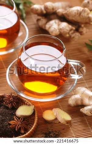 ginger tea in glass cup with ingredients around