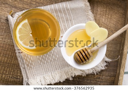 Ginger tea with lemon and honey on a wooden tray. Top view.  - stock photo