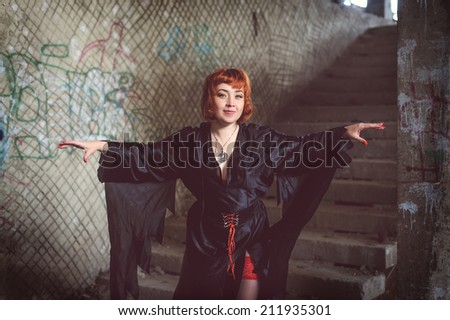 Ginger woman in black mantle in abandoned building - stock photo