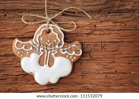 Gingerbread angel hanging over wooden background - stock photo