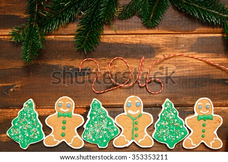 Gingerbread Christmas  cookies with fin's branch on the wooden background