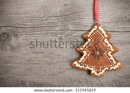 Gingerbread christmas tree hanging over wooden background - stock photo