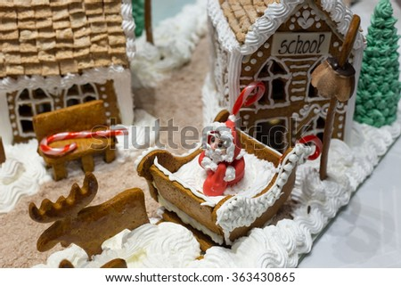 Gingerbread Christmas Village with Marzipan Santa in Sleigh  - stock photo