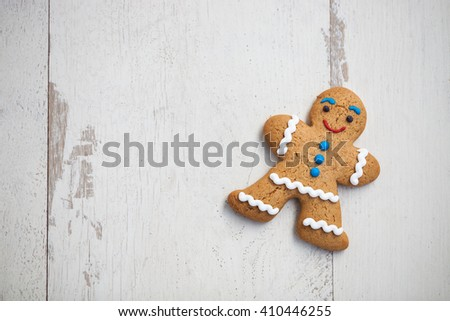Gingerbread cookie in shape of person lying on wooden table. Smiling eatable character with good taste. Close up macro, copy space on bright white wood - stock photo