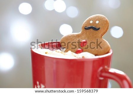 Gingerbread cookie men in a hot cup of cappuccino - stock photo
