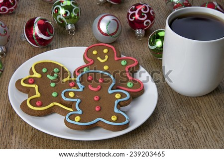 Gingerbread cookie men on a plate with a cup of coffee and Christmas Ornaments in the background on a wood table - stock photo