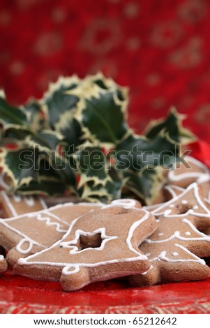 Gingerbread cookies and holly twig on Christmas background. Shallow dof - stock photo