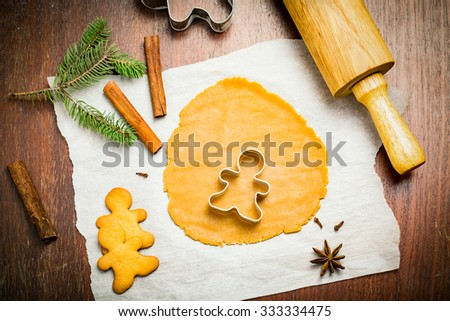 Gingerbread cookies, cookie dough and Christmas decorations on wooden table, high angle view - stock photo