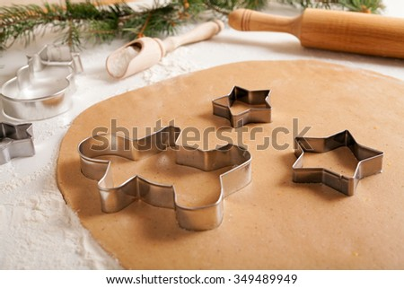 Gingerbread cookies dough preparation recipe with man shape and star forms, cinnamon rolling pin and flour on white kitchen table. Traditional homemade christmas dessert - stock photo