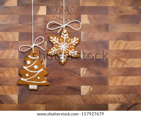 Gingerbread cookies hanging by twine over a wooden background