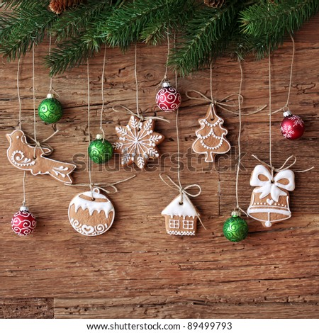 Gingerbread cookies hanging over wooden background - stock photo