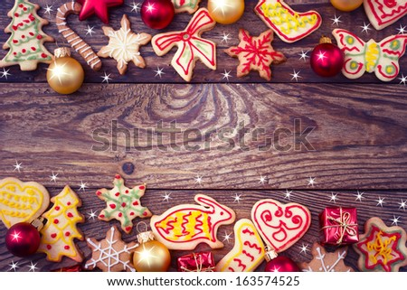 Gingerbread cookies hanging over wooden background. Christmas card - stock photo