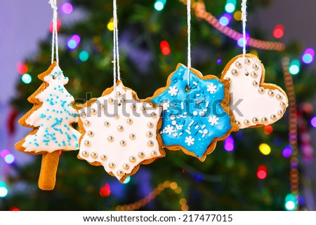 Gingerbread cookies hanging with Christmas tree on background - stock photo