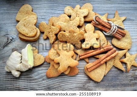 Gingerbread cookies in shapes of heart, star and man with cinnamon stick and ginger root on wooden table - stock photo