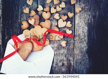 Gingerbread Cookies in the Shape of Heart from Letter with Red Ribbon on Wooden Table. Love Valentine Day concept. Toned - stock photo