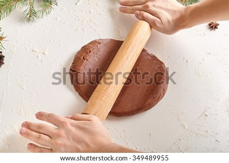 Gingerbread cookies preparation recipe, unrecognizable woman hands making dough with rolling pin on white kitchen table. Traditional homemade christmas dessert - stock photo
