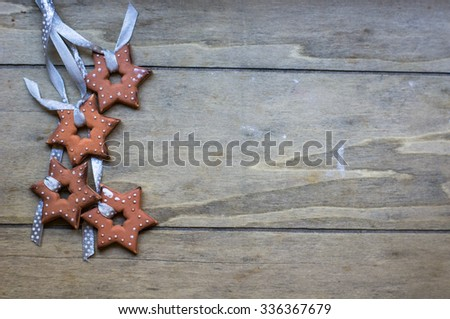 Gingerbread cookies star shaped hanging on the ribbon over wooden background - stock photo
