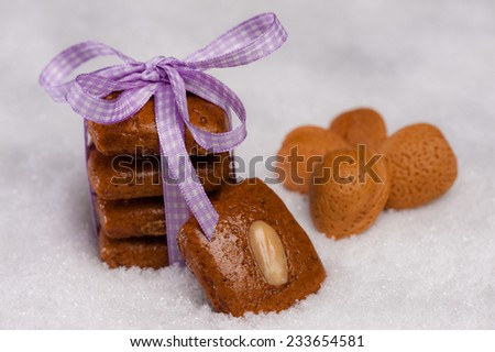 Gingerbread cookies tied with a violet ribbon on artificial snow. Almonds lying beside. - stock photo