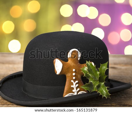 gingerbread figure with holly branch on the black hat in front of shiny background - stock photo