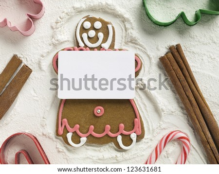Gingerbread girl holding an empty white card - stock photo