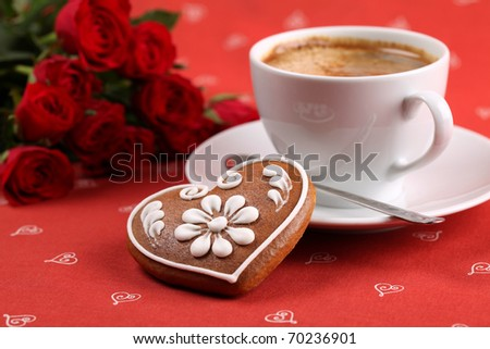 Gingerbread heart with coffee and red roses on red background. Shallow dof - stock photo
