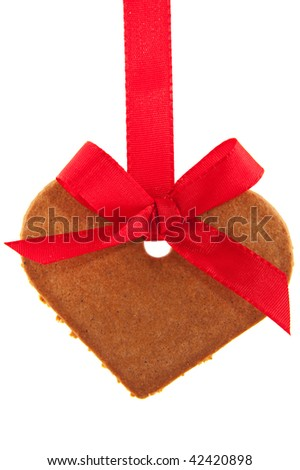 Gingerbread heart with red ribbon hanging as a garland