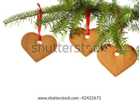 Gingerbread hearts hanging under fir branch and isolated against white background - stock photo