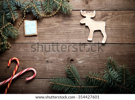 Gingerbread homemade cookies with icing and christmas tree branch on a wooden table or board for background. New year theme. Toned.