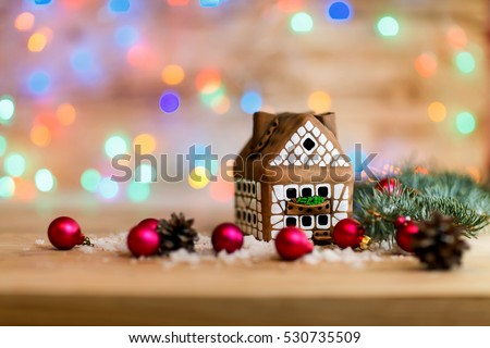 gingerbread house and Christmas balls on festive background. the photo has a empty space for your text