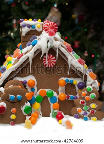 Gingerbread house and Christmas tree in the background - stock photo