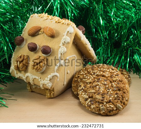 Gingerbread house and oatmeal cookies on the board - stock photo